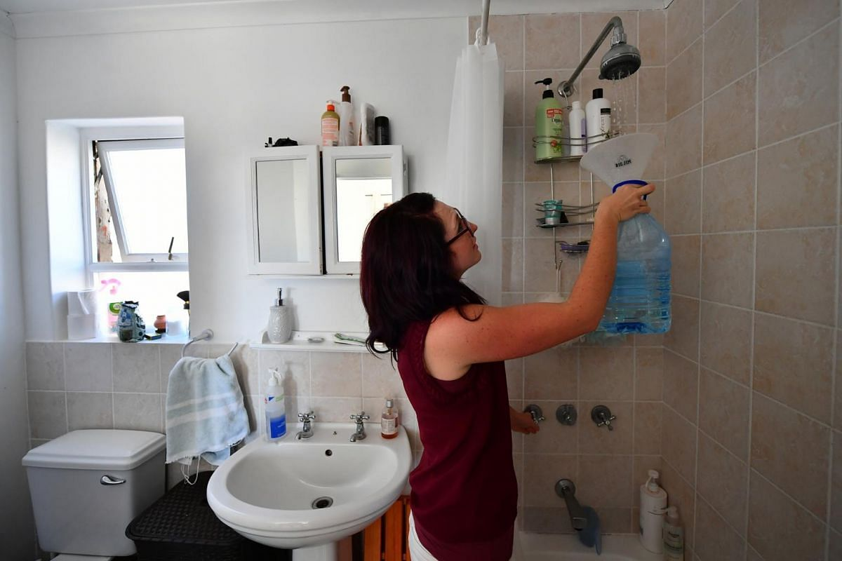 Mrs Bronwyn Kerswill, 31, a medical sales representative, collecting drinkable water before bathing, at her house on June 5, 2018.
