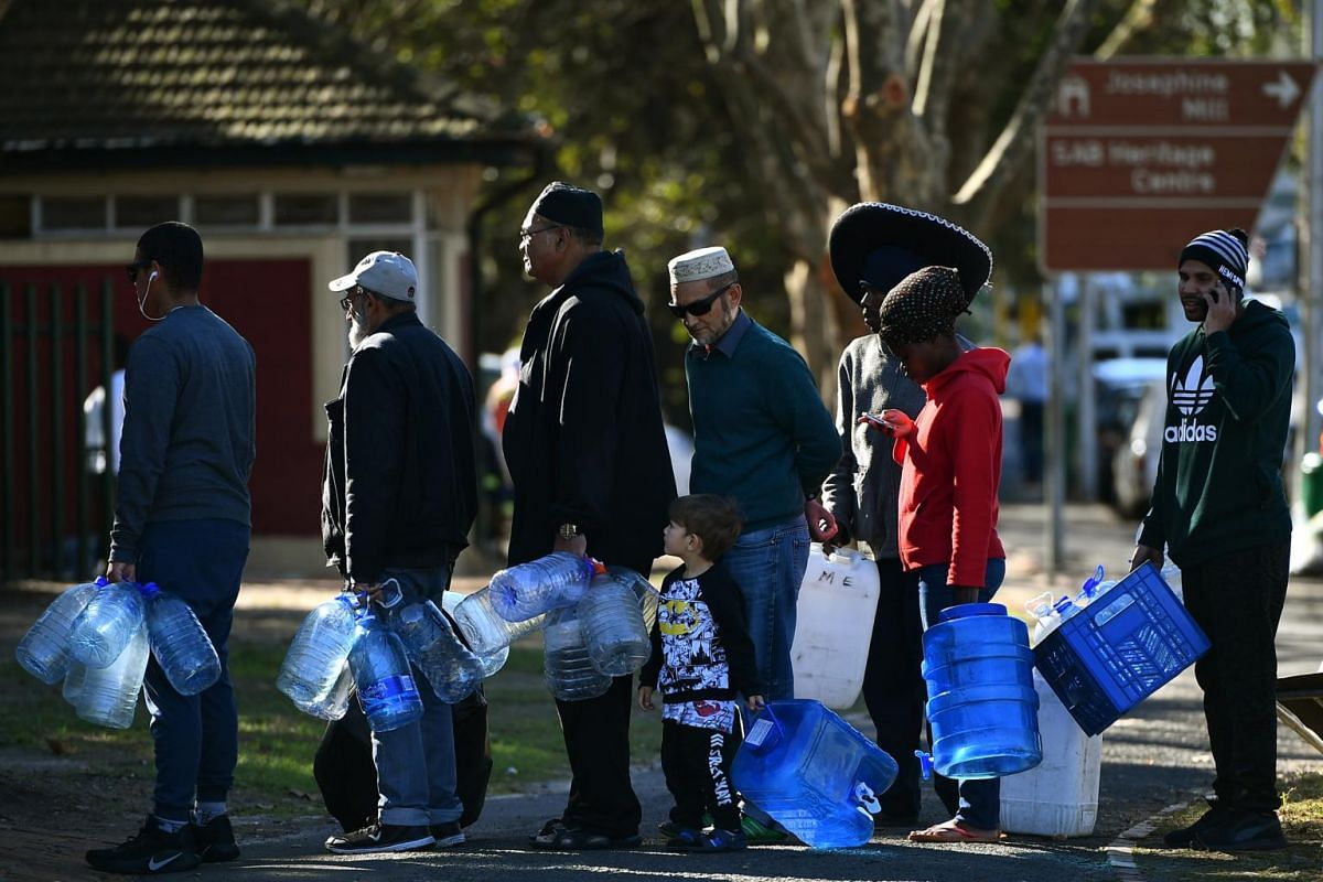 People queueing to get their water rations from the spring water collection point at Newlands swimming pool in Cape Town, on June 4, 2018.