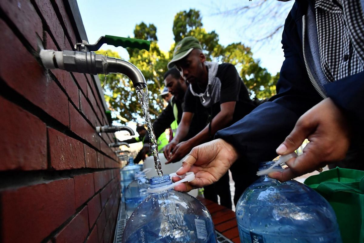 People getting their water rations from the spring water collection point at Newlands swimming pool in Cape Town, on June 4, 2018.