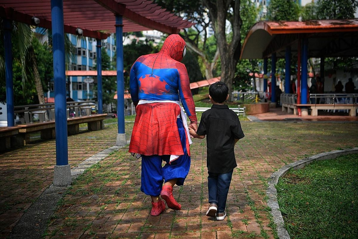 Volunteer cosplayer Mohamad Faizal Mohamad Rafi, 33, dressed up as Spider-Man, with a birthday boy at a party in April.