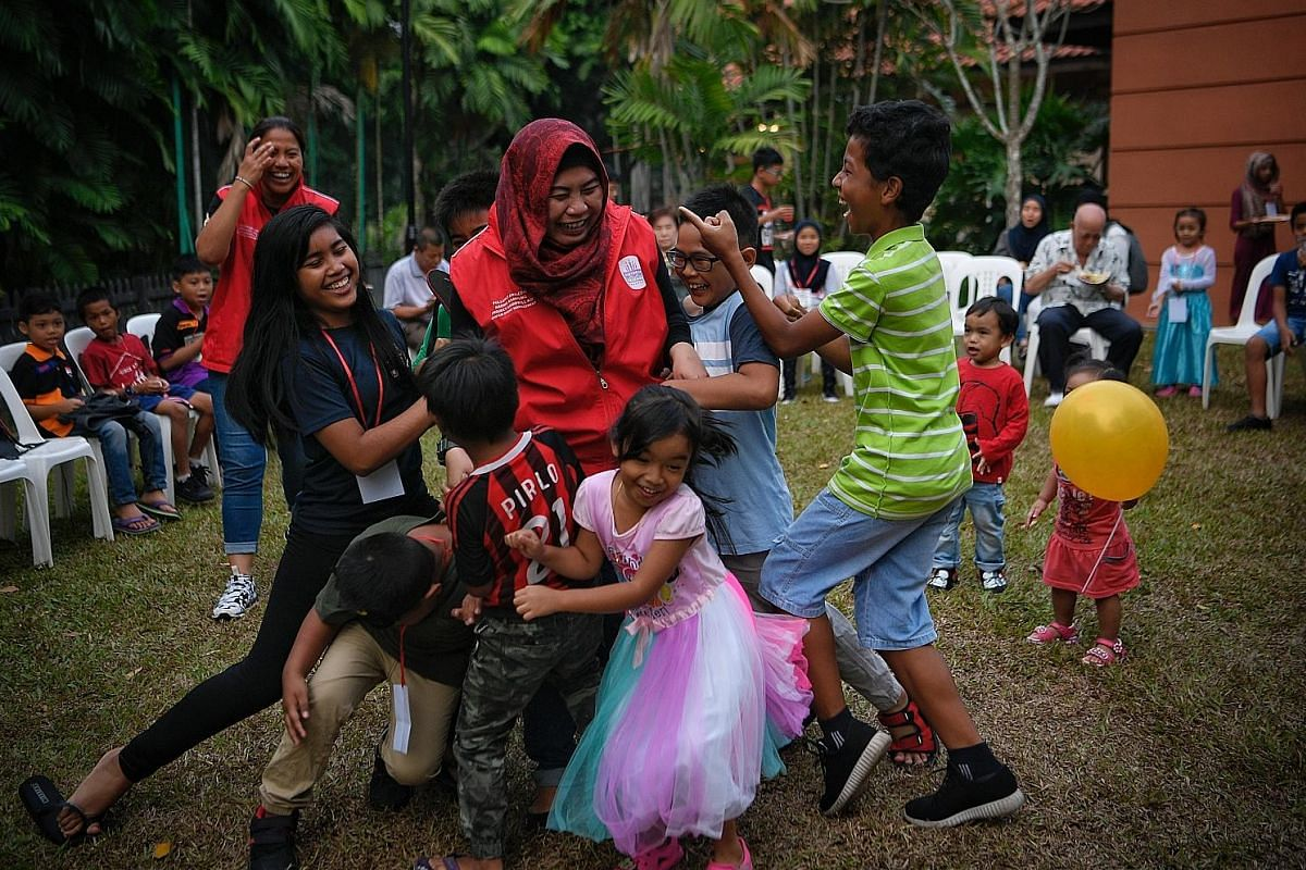 Sisters Nuraini Asmawi (foreground), 37, and Nurhayati Asmawi, 34, (background, in red vest) playing games with the children during a mega bash for the kids at Project Goodwill Aid's anniversary earlier this year, where they collaborated with Birth