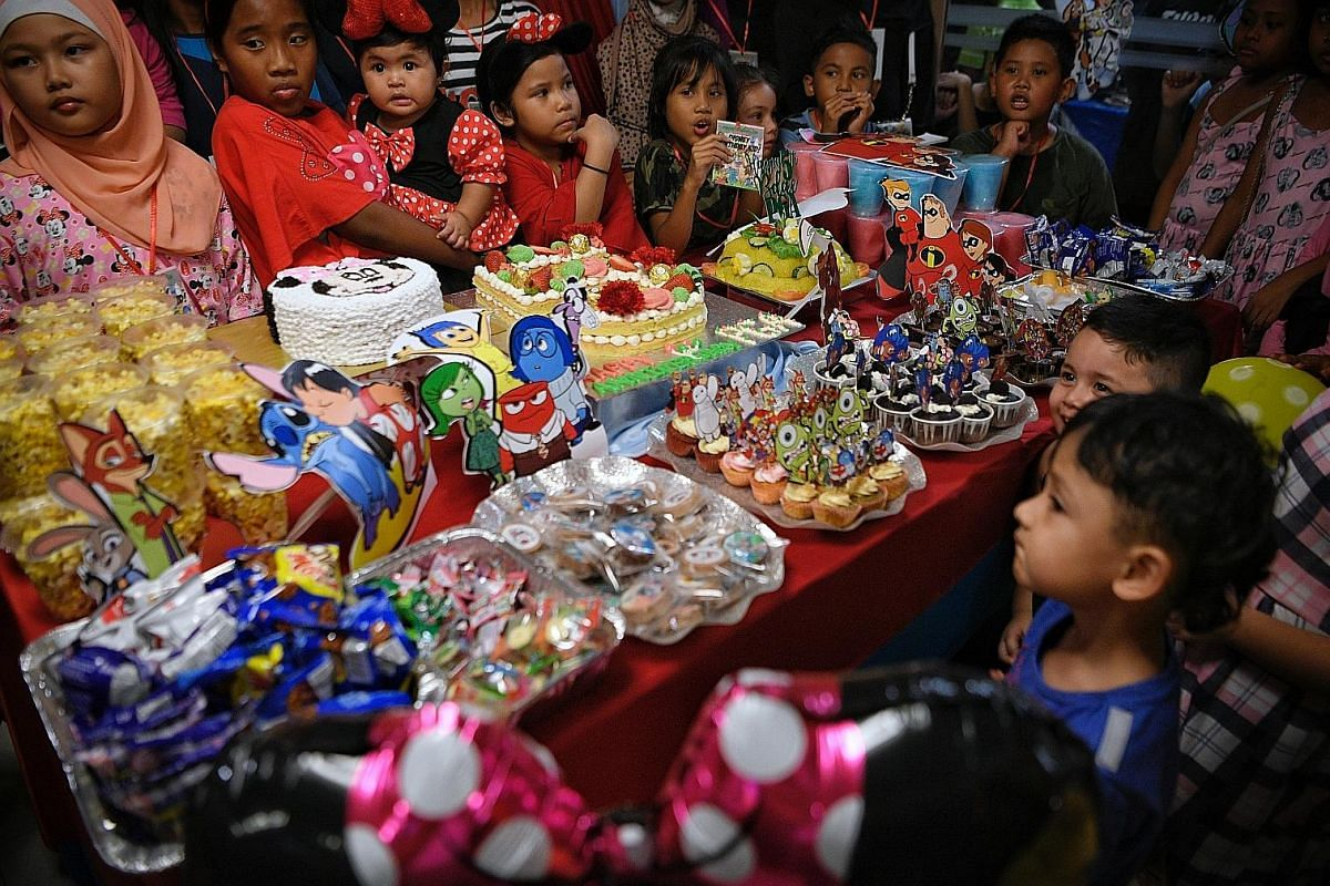 Children and guests crowding round a table laden with cakes and goodies at a birthday bash for March kids, with 250 guests, at a chalet earlier this year. Most of BBSG's birthday kids are recommended by the volunteer group.