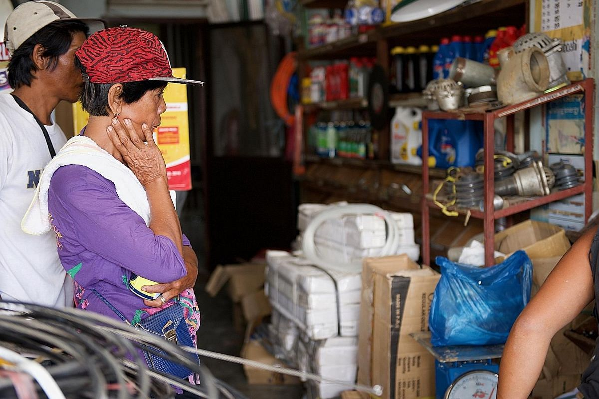 Ms Remigios Casay, 64, a farmhand, queueing for construction materials such as iron sheets, plywood, nails and a hammer that she needs to rebuild her home, which was destroyed by Typhoon Mangkhut Volunteers rebuilding a house destroyed by the typhoon