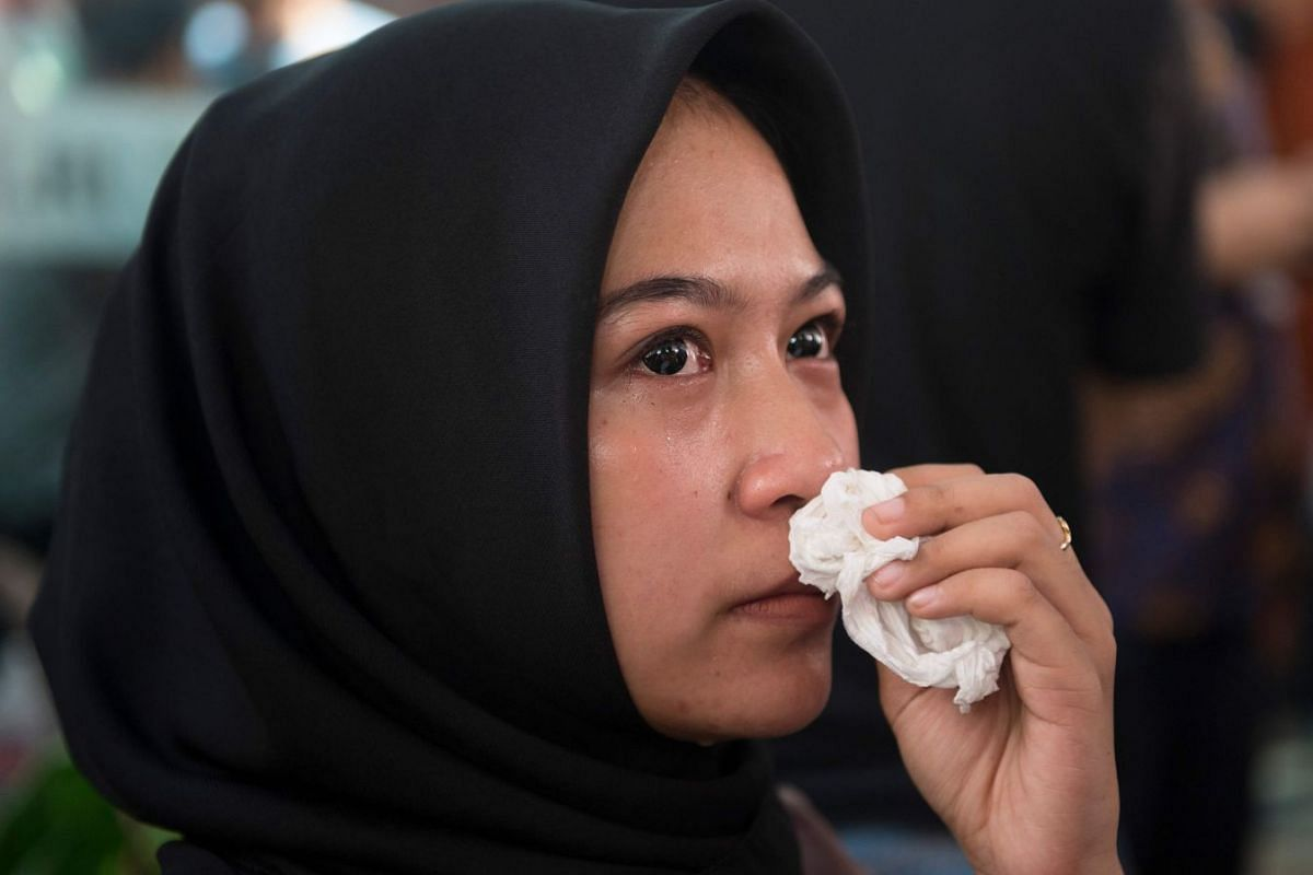 A girl mourns for her father who was on board the plane as she submits his papers and photographs at a disaster victim identification unit at a police hospital in Jakarta on Oct 30, 2018.
