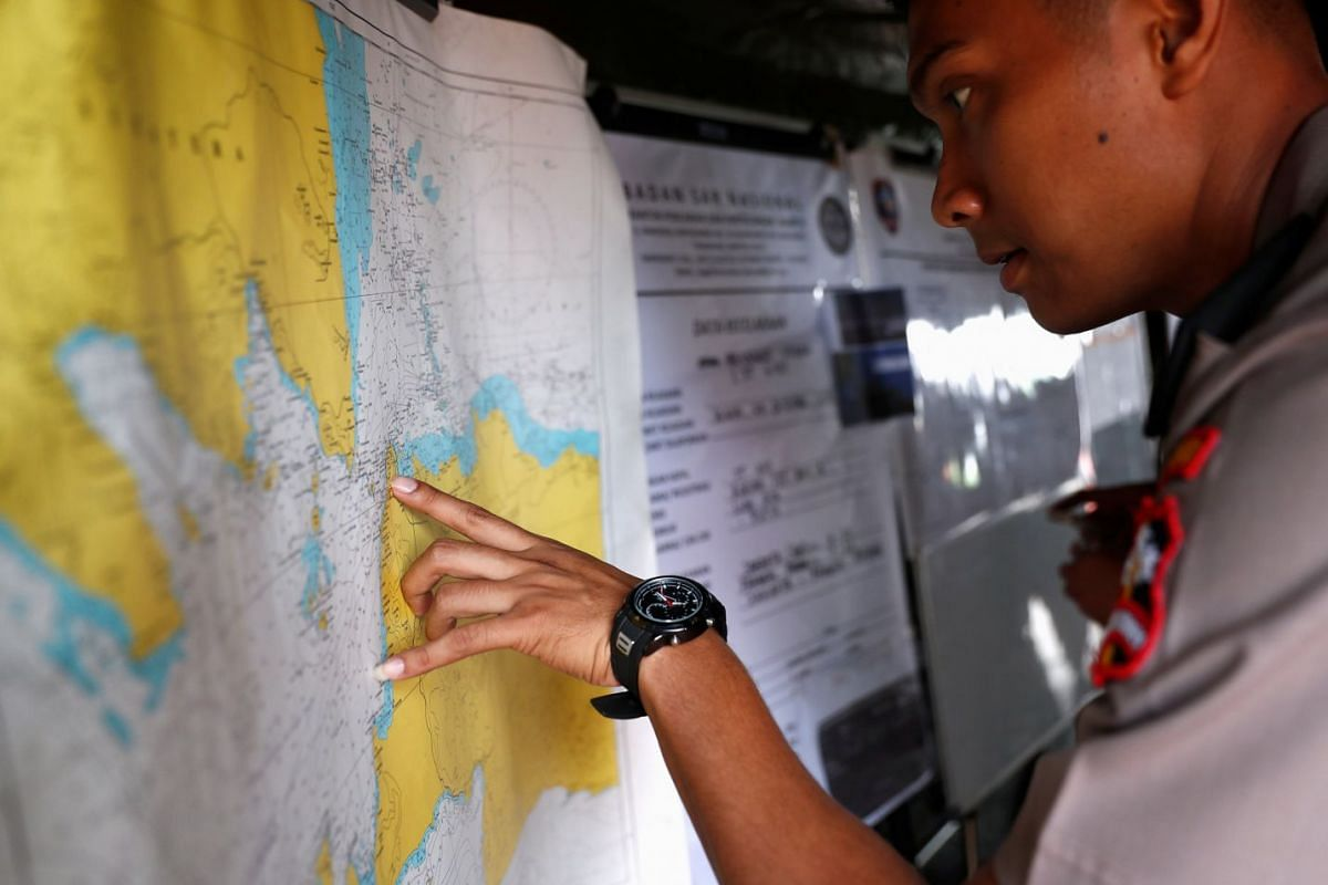 An Indonesian police officer studies a map in the search and rescue command centre at Tanjung Priok port in Jakarta on Oct 30, 2018.