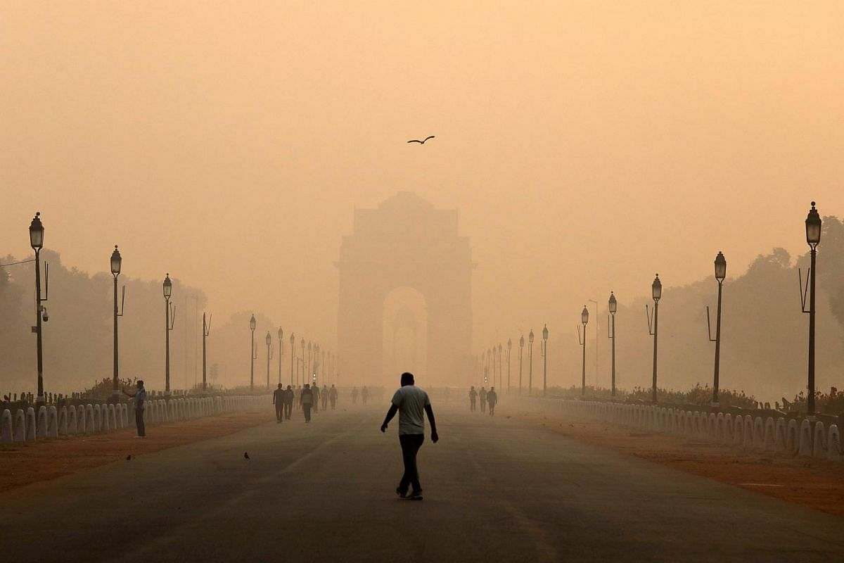 A man walks in front of the India Gate shrouded in smog in New Delhi, India, on Oct 29, 2018.