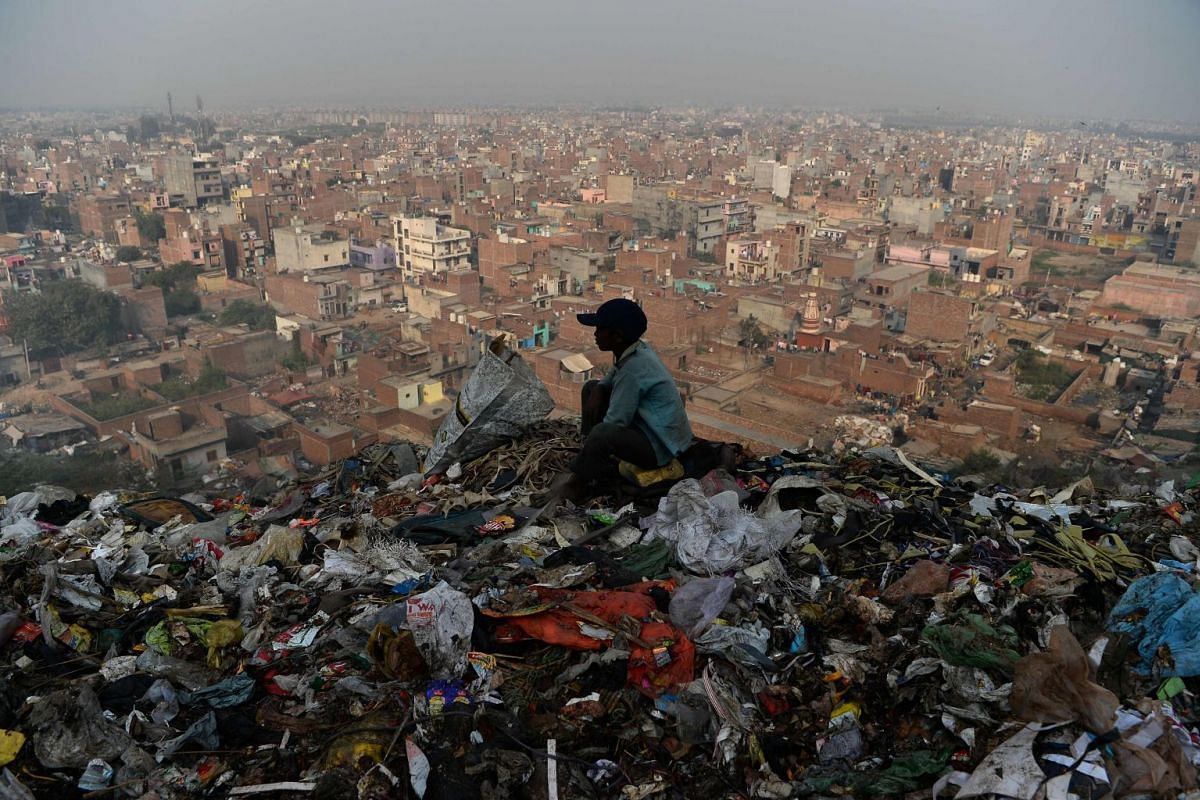 A young Indian ragpicker looks over the city after collecting usable material from a garbage dump at the Bhalswa landfill site in New Delhi, India, on Oct 29, 2018.
