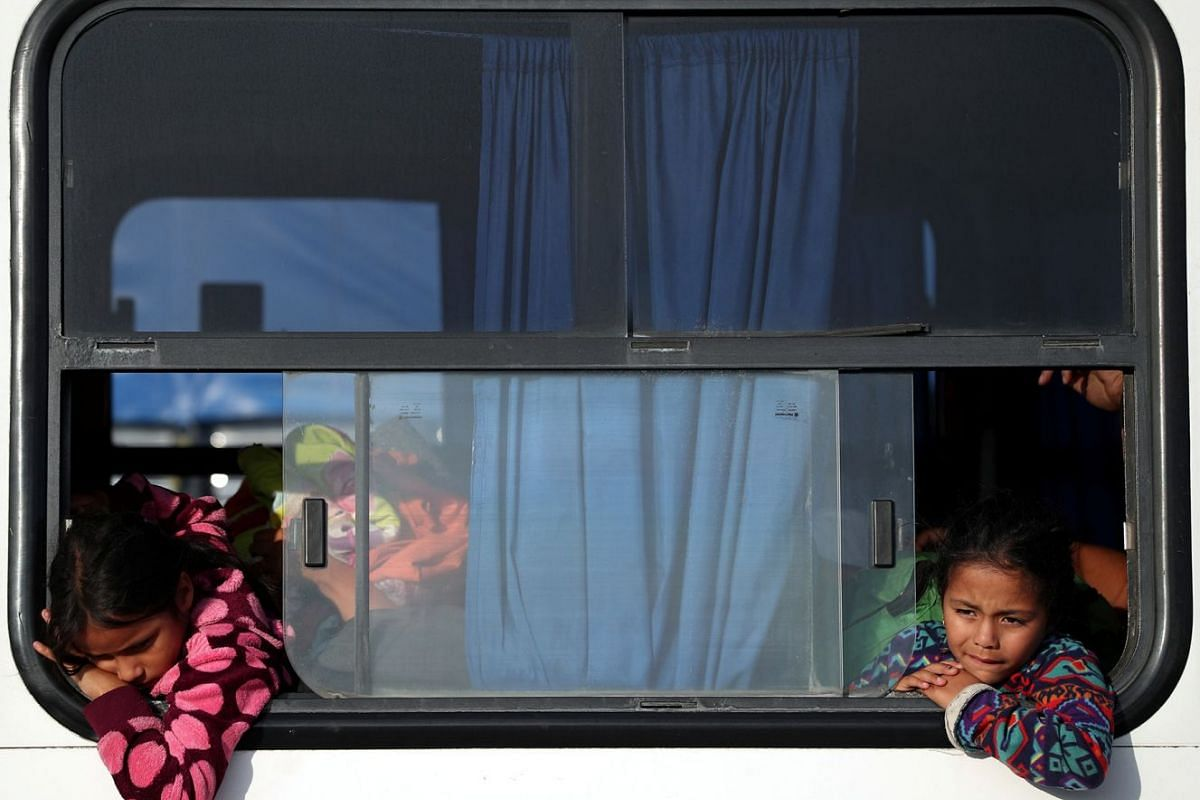 Migrants Isis Alexandra, aged 8 and Amanda Garcia, aged 6 from Honduras, part of a caravan of thousands from Central America en route to the United States, travel on a bus as they are transported to Juchitan from Santiago Niltipec, Mexico, October 30