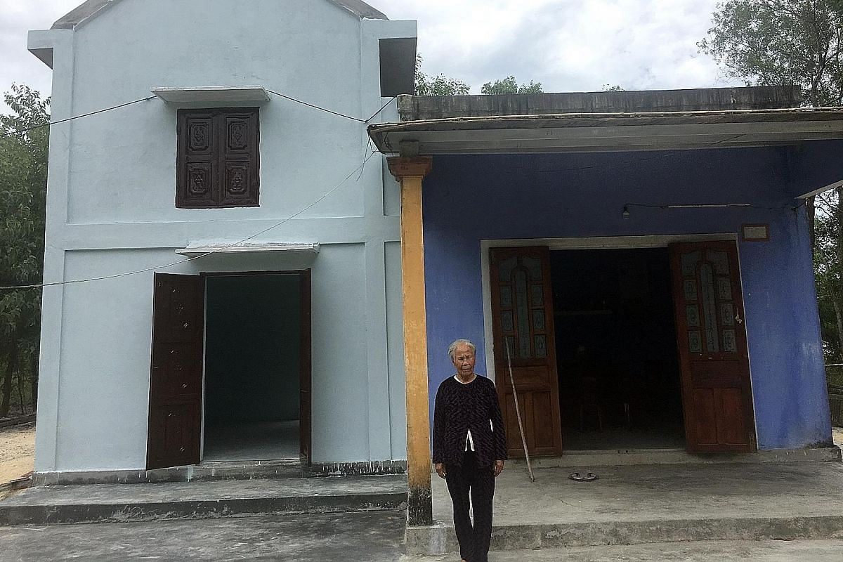 Mrs Nguyen Thi Thi, 81, in front of her old house (in blue). Her new two-storey house next door - built under a storm-proof housing scheme - is sturdier, with a second floor for her to take refuge when flooding hits her village in Hue province. Farme