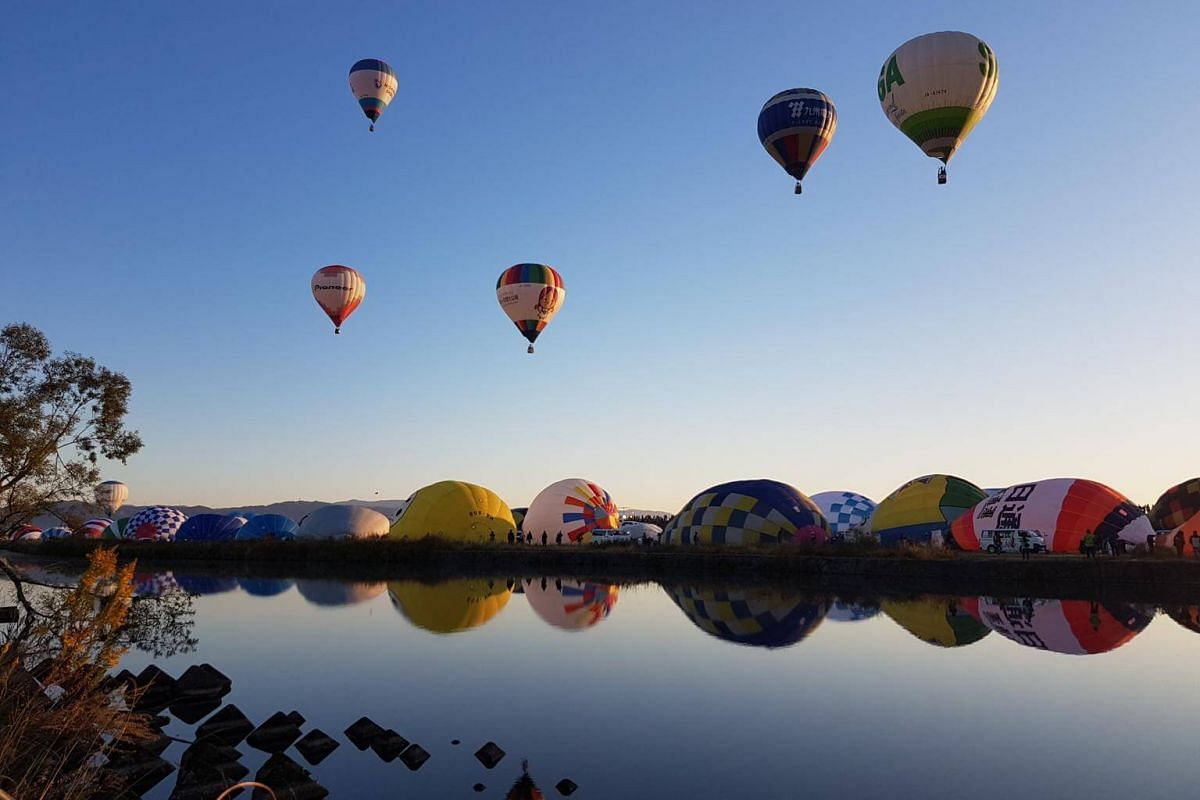 Balloons are inflated along the Kasegawa River during the morning run of the competition at the Saga International Balloon Fiesta on Nov 3, 2018.