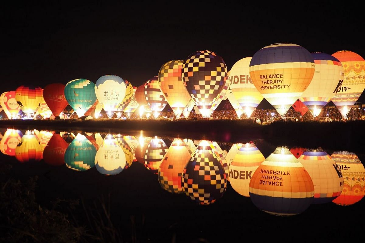 Inflated balloons are lit in tune with music along the Kasegawa River during the La Montgolfier Nocturne (Night Mooring) at the Saga International Balloon Fiesta on Nov 3, 2018.