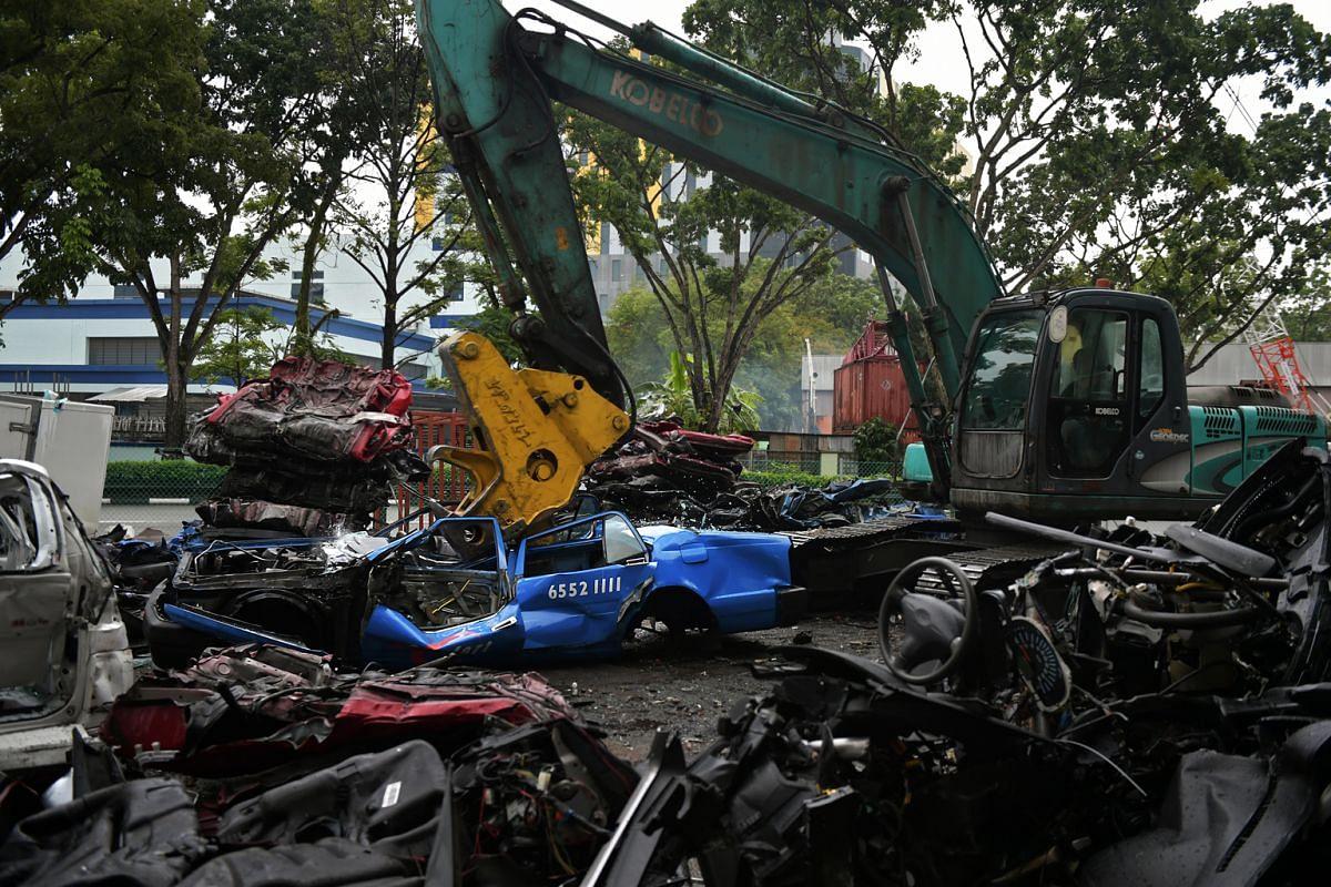 Above: A crane flattening the Crown taxi at the Kheng Kheng scrapyard.