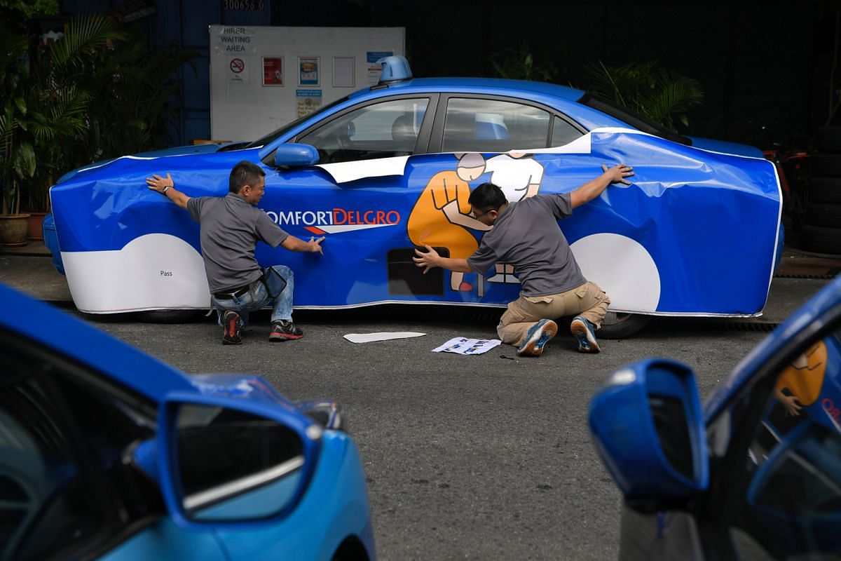 Moove media employees Chong Wee Siong (left), 37, and Lim Hua Seng, 36, covering the Sonata with vinyl stickers before it was sent to the Salvation Army's Peacehaven Nursing Home last month.