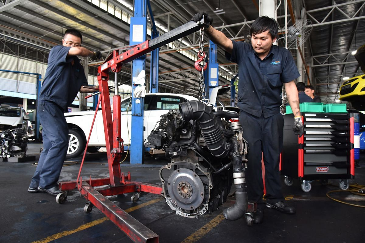 Mechanics Gao Fei (left), 32, and Yam Kang Min, 24, removing the engine of a Hyundai Sonata taxi. It takes them about an hour to complete the job.