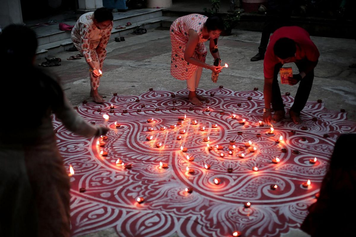 Lamps being lit up on a painted floor as part of the Festival of Lights in Kolkata, eastern India, on Nov 6, 2018.