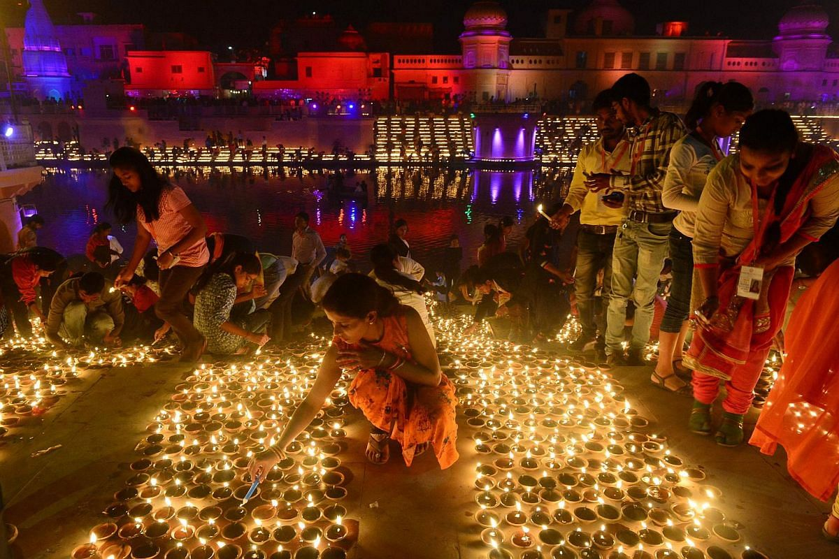Devotees lighting up earthen lamps on the banks of the River Sarayu on the eve of the Deepavali festival during a Deepotsav event organised by the Uttar Pradesh government in Ayodhya on Nov 6, 2018.