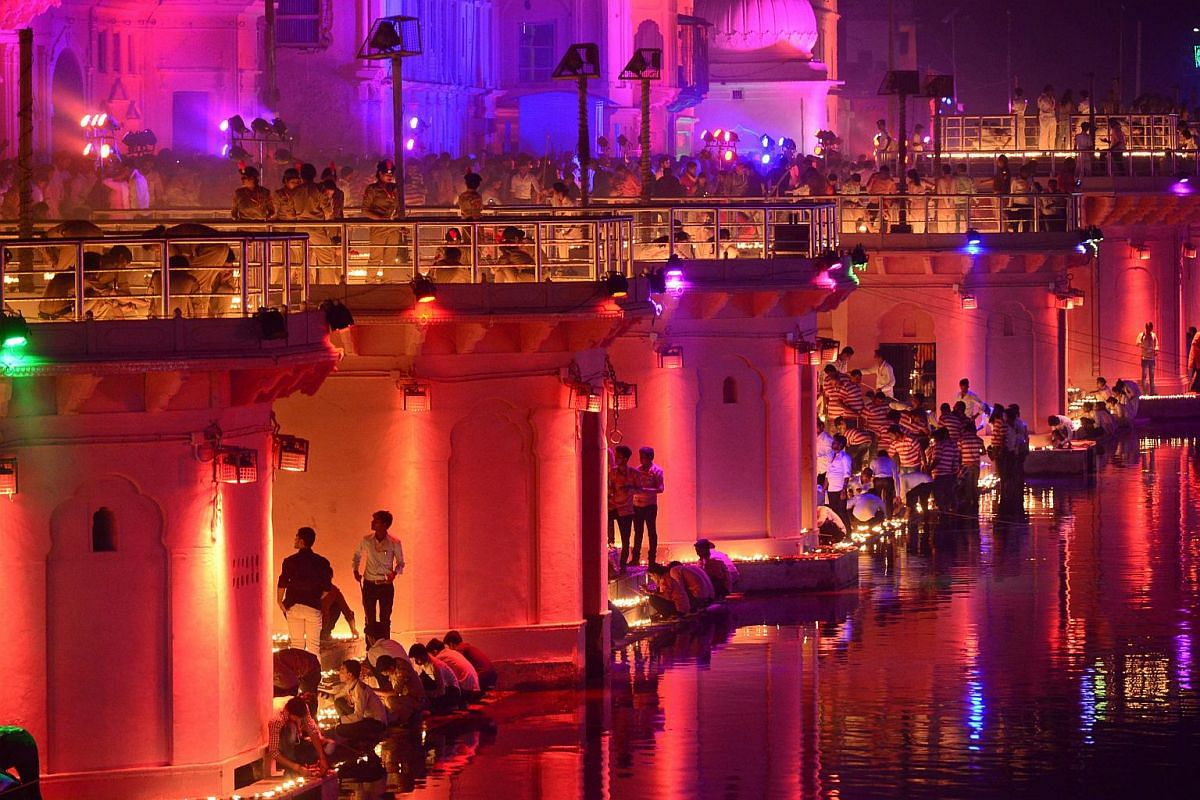 Devotees lighting up earthen lamps along the banks of the River Sarayu on the eve of Deepavali during a Deepotsav event organised by the Uttar Pradesh government in Ayodhya on Nov 6, 2018.