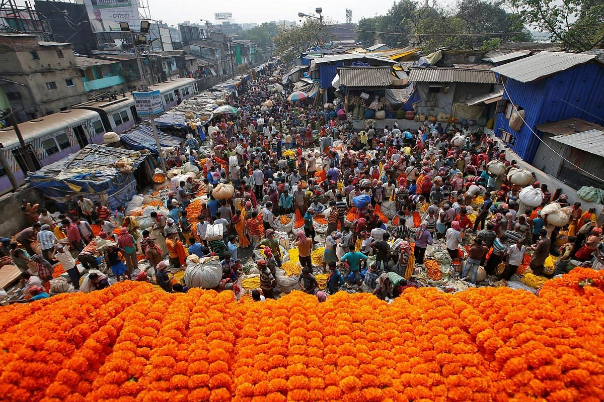 Vendors selling marigold garlands, which are used to decorate temples and homes, on the eve of Deepavali in Kolkata, India, on Nov 6, 2018.