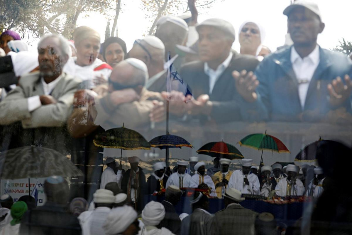 Members of the Israeli Ethiopian community are seen through a glass panel during a ceremony marking the Ethiopian Jewish holiday of Sigd in Jerusalem on Nov 7, 2018.