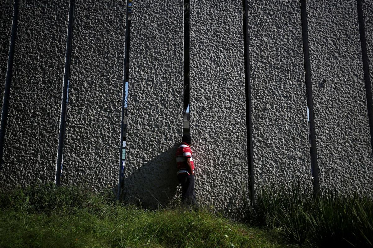 A migrant, part of a caravan of thousands of people making their way from Central America to the United States, looking at Mexico City, Mexico, through a wall in a makeshift camp on Nov 7, 2018.