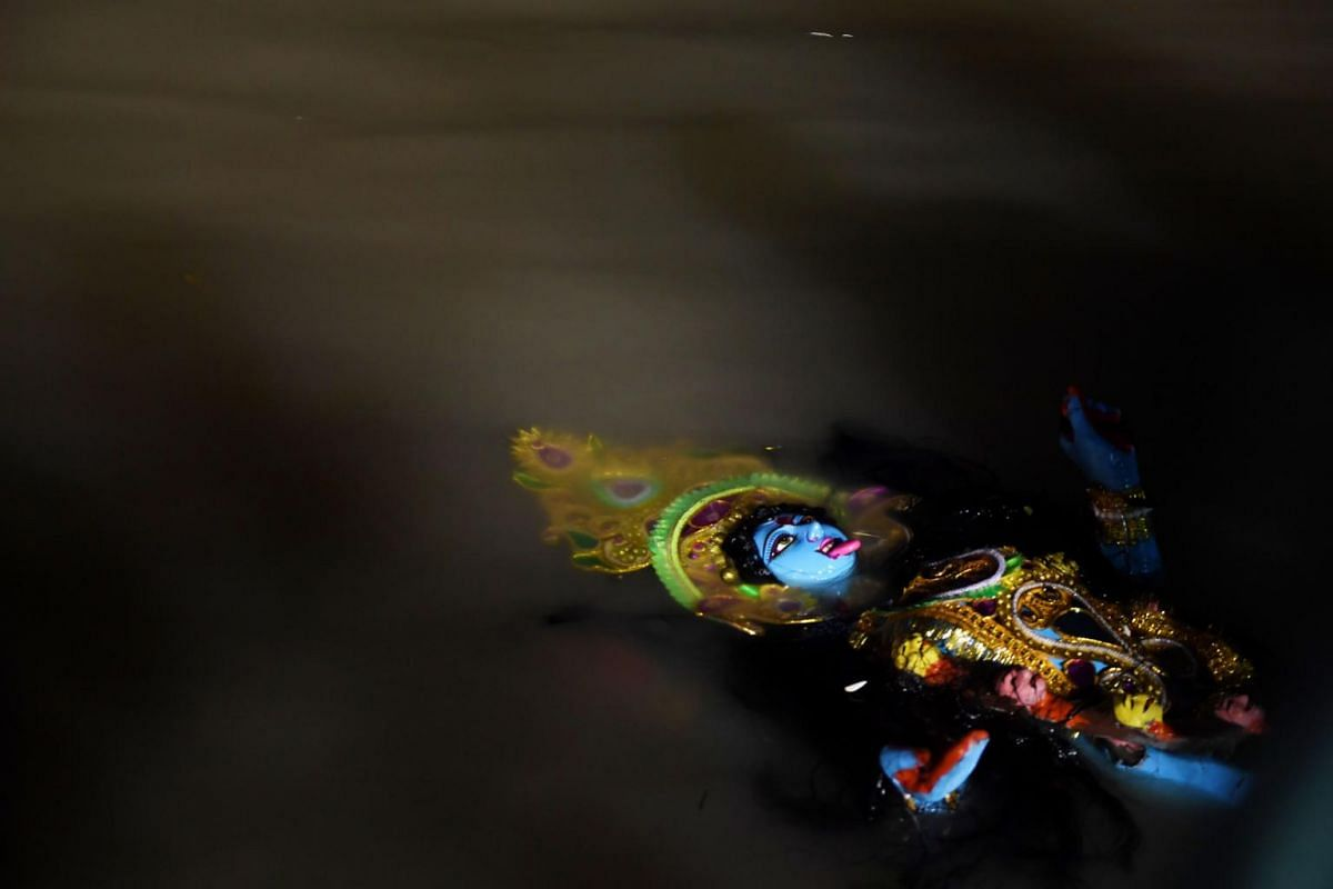 """Devotees immersing an idol of the Hindu Goddess Kali in the holy river of Ganges to mark the end of the  """"Kali Puja"""" festival in Kolkata on Nov 7, 2018."""