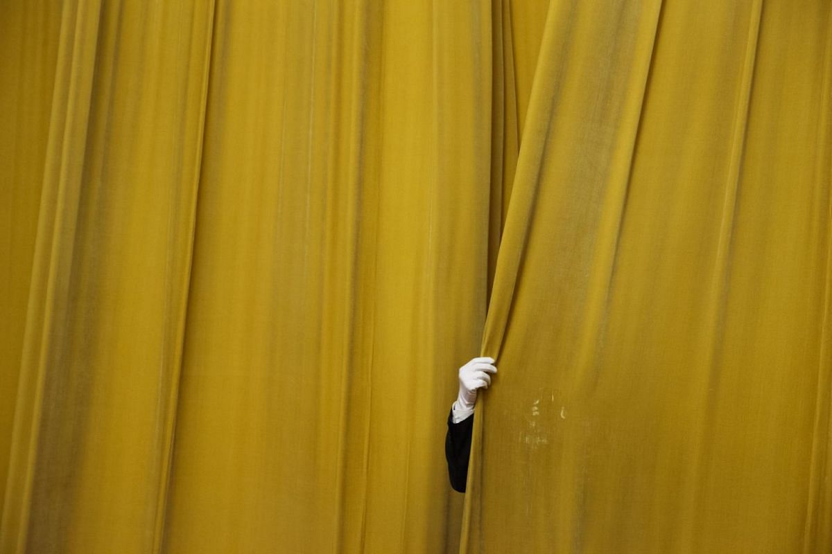 A Chinese security official drawing the curtains at the Great Hall of the People before a meeting between former US Secretary of State Henry Kissinger and China's President Xi Jinping in Beijing, China, on Nov 8, 2018.