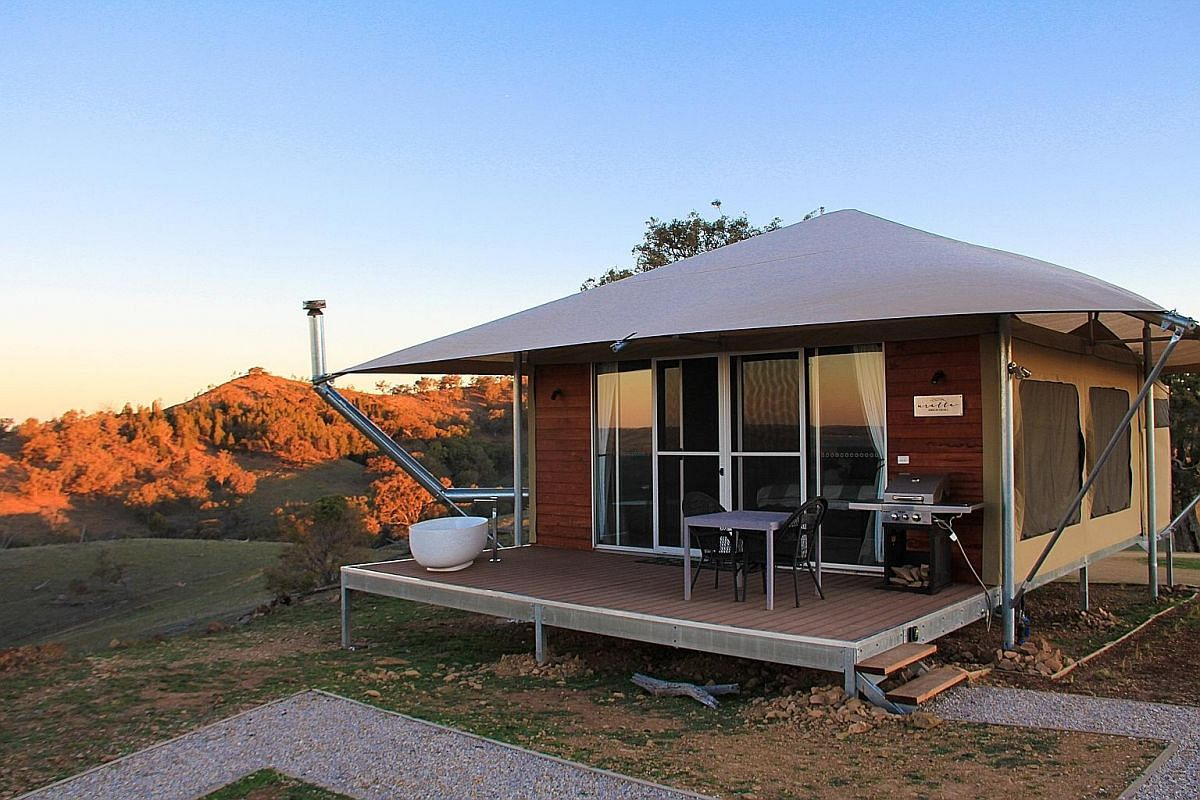 Above: At Birubi Point, take a ride on a camel on Stockton Beach. Below: Hop on a dolphin-watching cruise at Port Stephens. Glamping site Sierra Escape has a tent with a bathtub on the verandah overlooking the Australian bush. Above: Take in the vast