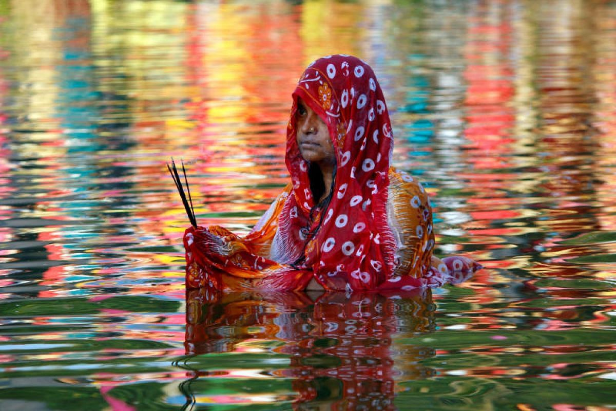 A Hindu woman worships the Sun god in the waters of a lake during the religious festival of Chhath Puja in Agartala, India, Nov 13, 2018. PHOTO:REUTERS