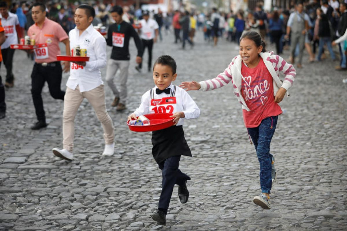 People participate in a waiters and waitress run in Antigua Guatemala, Guatemala Nov 14, 2018. PHOTO:REUTERS