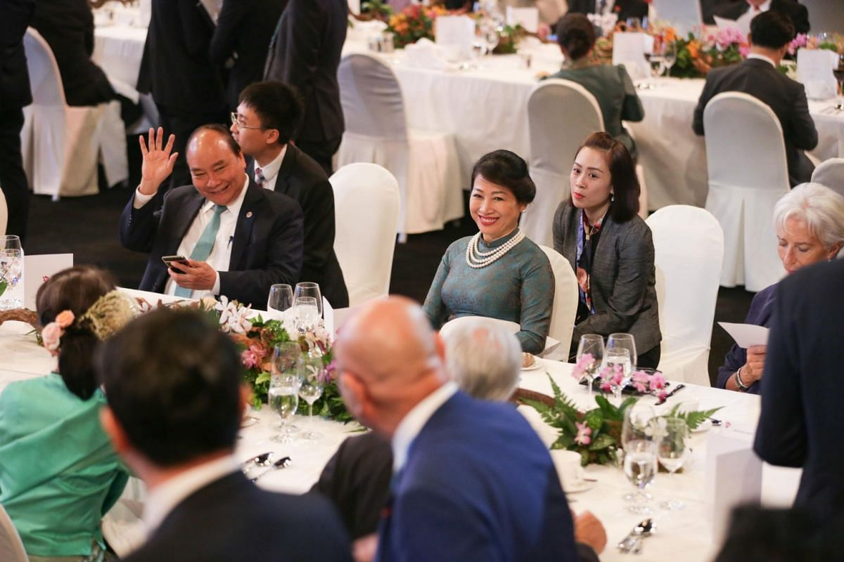 Vietnam Prime Minister Nguyen Xuan Phuc (left) waves as someone walks by his table at the Asean Summit gala dinner. Next to him is his wife Madam Tran Nguyet Thu.
