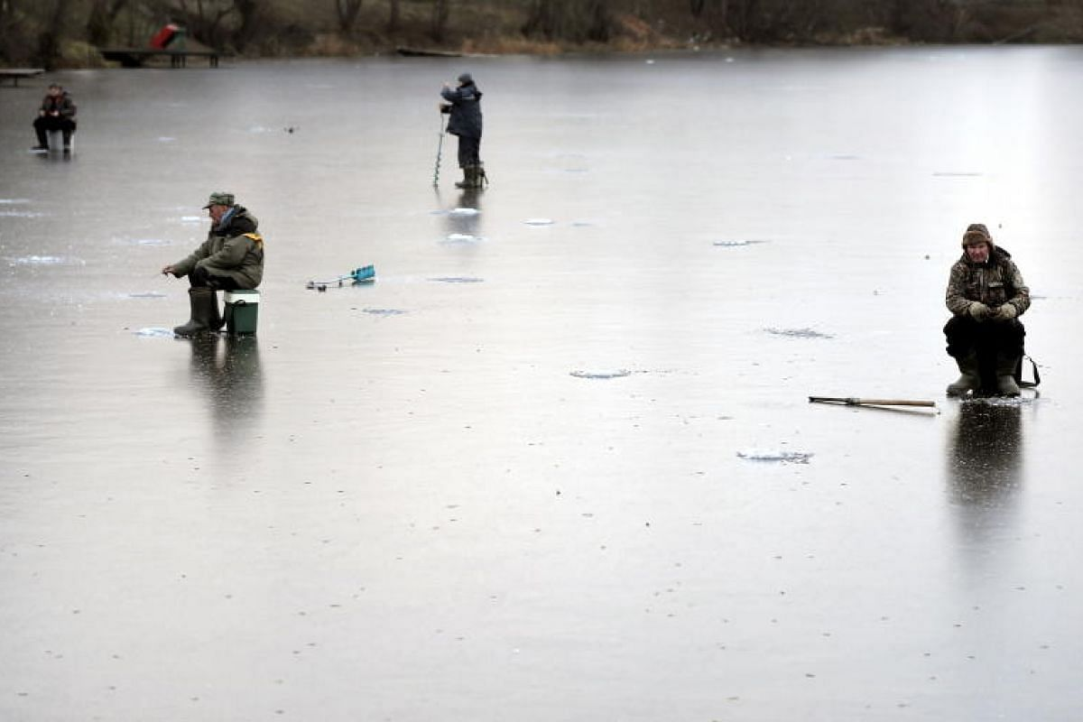 Some men fishing on a first thin ice on a pond as temperatures plunged to minus 8 degrees Celsius in Moscow, Russia on 15 Nov, 2018. PHOTO:EPA-EFE