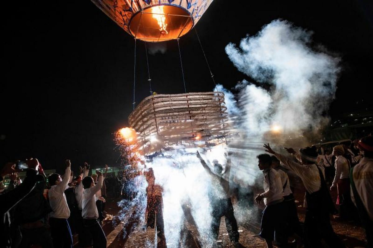 Participants releasing a hot-air balloon carrying small lanterns during the Tazaungdaing Lighting Festival at Taunggyi in Myanmar's northeastern Shan State. Brightly coloured balloons with hundreds of homemade fireworks woven into their frames are se