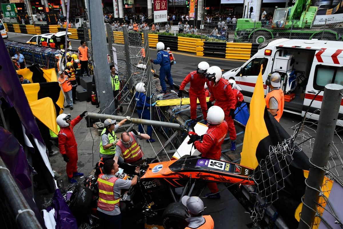 Race personnel and pit crew are seen at the accident site after Sophia Floersch, a German driver of Van Amersfoort Racing flew over the barriers and crashed into a photographers' bunker at high speed, during a Formula Three race at the Macau Grand Pr