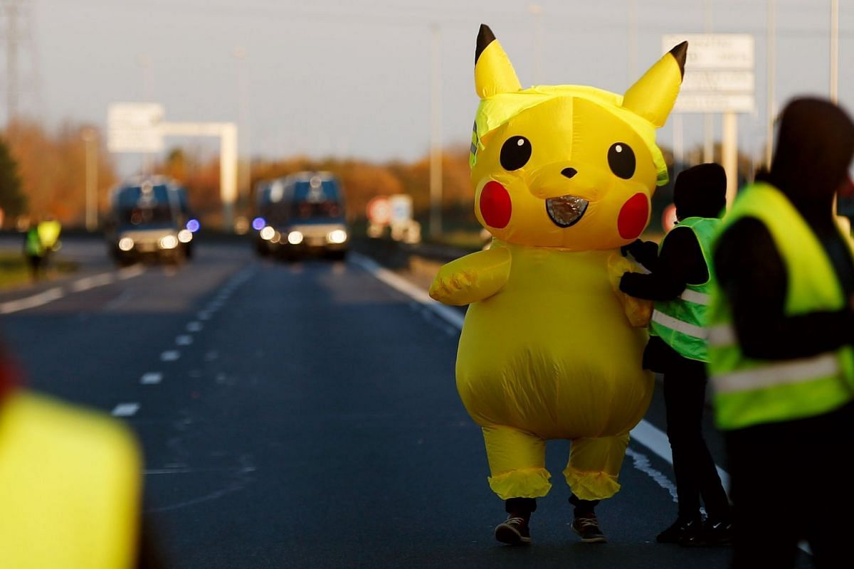 People and a mascot of Pikachu stand in front of gendarme's trucks on Caen's circular road on November 18, 2018 in Caen, northwestern France, on a second day of protest. PHOTO: AFP
