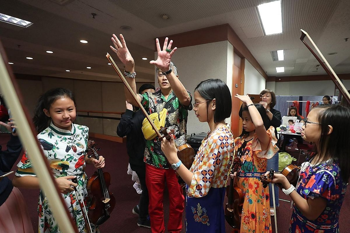 Some performers stretching out on Nov 11, one of the combined rehearsal sessions for ChildAid 2018. Performer Adriana Balqis (left), nine, touching up the make-up of fellow performer Chloe Wong Yu Xuan, eight, before the full-dress rehearsal yesterda