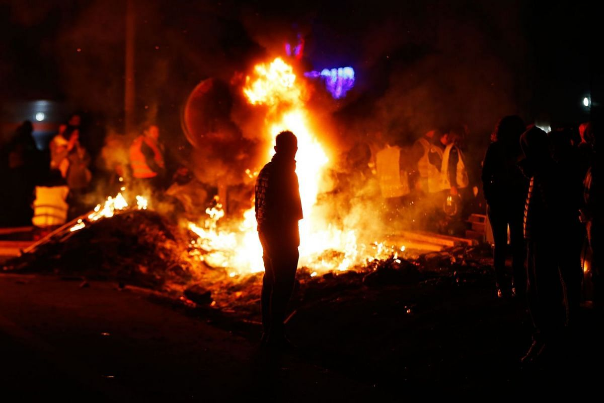 Protesters stand around a fire as they block the ring road of Caen, northwestern France, on November 18, 2018, on a second day of demonstrations. PHOTO: AFP