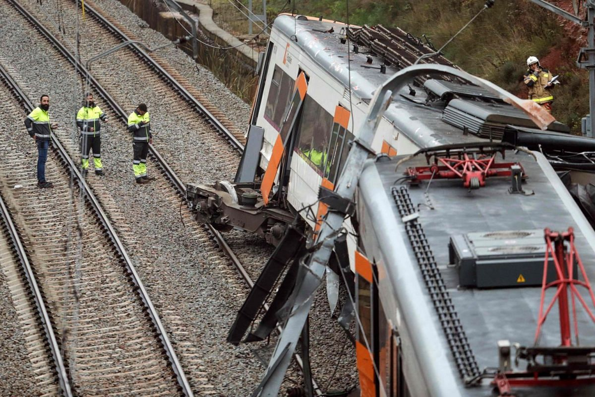 Personnel stand at the site where a commuter train derailed in the town of Vacarisses, about 35 kilometres (20 miles) northeast of Barcelona, on November 20, 2018. PHOTO: AFP