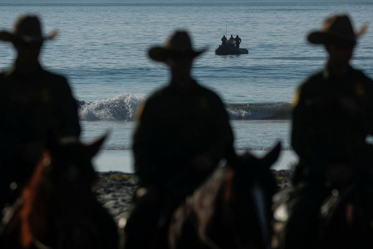 U.S. Border agents patrol the Pacific Ocean as other agents ride horses next to the border with Mexico at Border Field State Park in San Diego, California, U.S. November 20, 2018. PHOTO: REUTERS