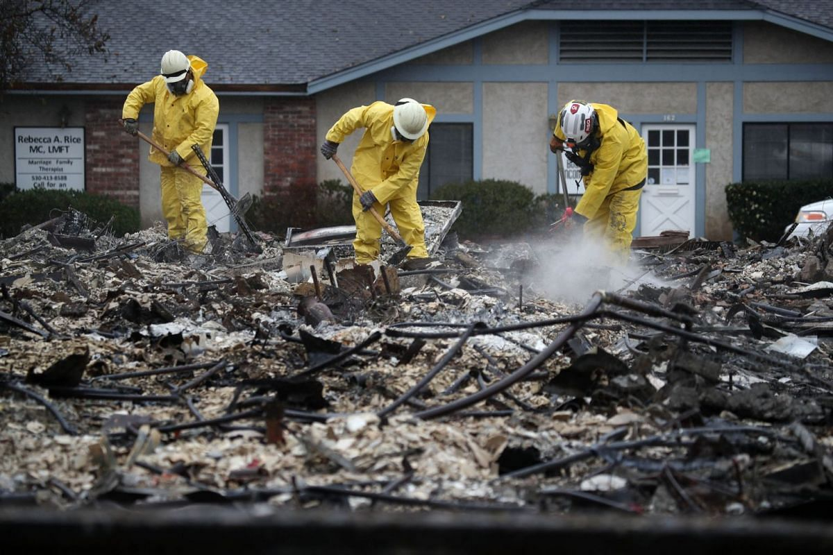 Search and rescue crews dig through the burnt remains of a business as they search for human remains on November 21, 2018 in Paradise, California. PHOTO: GETTY IMAGES/AFP