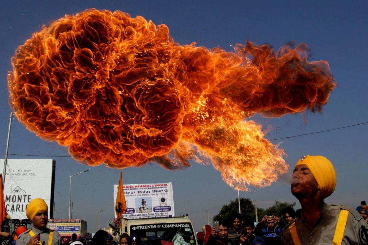 An Indian Sikh devotee spits fire as he performs during religious procession ahead of the birth anniversary of the first Sikh Guru or master, Sri Guru Nanak Dev Ji, the founder of Sikhism, in Jammu, the winter capital of Kashmir, India, 21 November 2