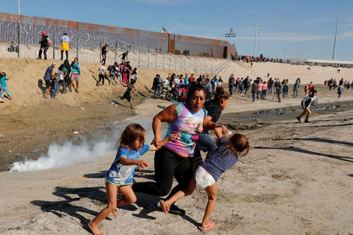 A migrant family, part of a caravan of thousands traveling from Central America en route to the United States, run away from tear gas in front of the border wall between the U.S and Mexico in Tijuana, Mexico, November 25, 2018.