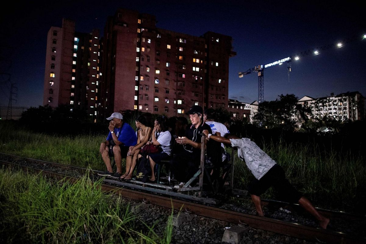 """This photo taken on October 19, 2018 shows a """"trolley boy"""" (right) pushing a home-made cart with passengers on a train track in Manila. Scores of commuters in the city of about 12 million are propelled to their destinations daily by so-called """"trolle"""