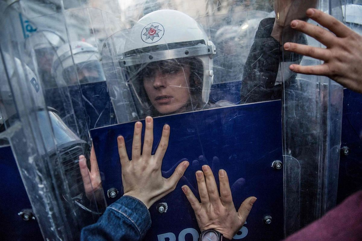 A Turkish female riot police officer reacts during clashes with women's rights activists as they try to march to Taksim Square to protest against gender violence in Istanbul, on November 25, 2018, on the International Day for the Elimination of Viole