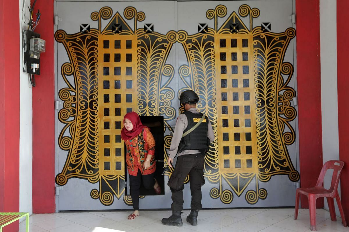 A police officer stands guard at the front door of the Banda Aceh Penitentiary in Lombaro, Banda Aceh, Indonesia, November 30, 2018. More than 100 inmates escaped from prison after breaking down several fences. According to media reports, police in A