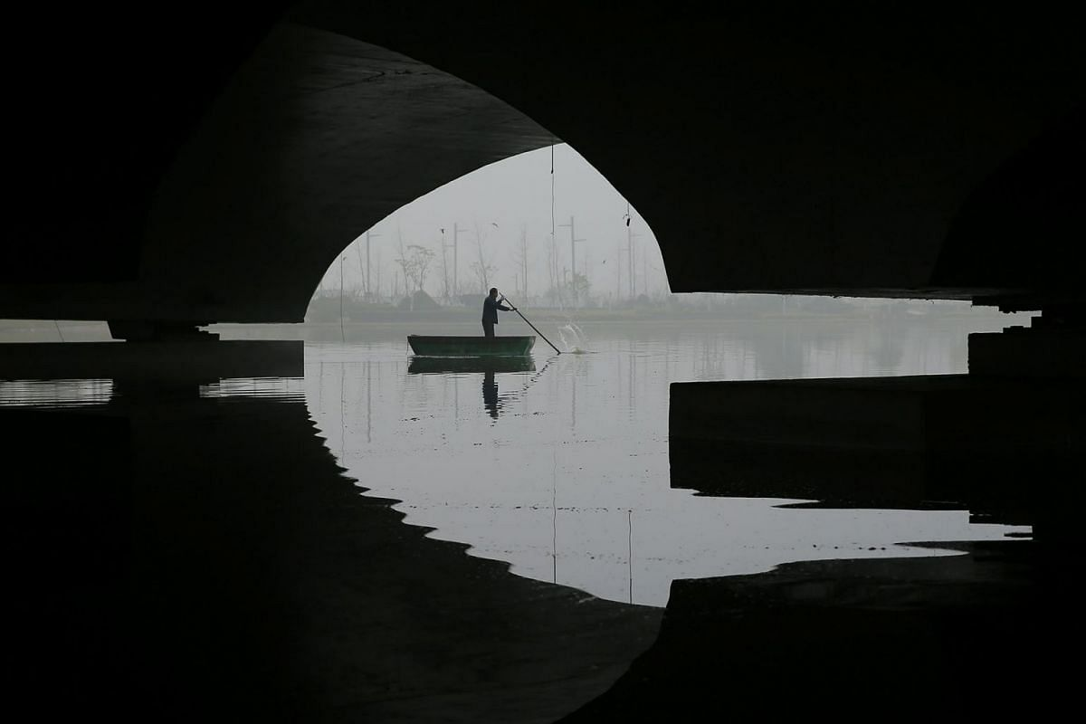 A man rows a boat on a foggy day after the orange alert for fog was issued in Lianyungang, Jiangsu province, China, November 29, 2018.