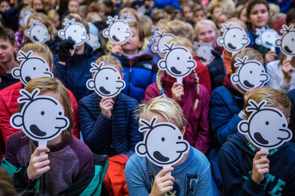 Children cover their faces with the fictional character, Greg Heffley, during a gathering with American cartoonist, producer and author of children's, Jeff Kinney (unseen), in Oslo, Norway, on November 29, 2018.
