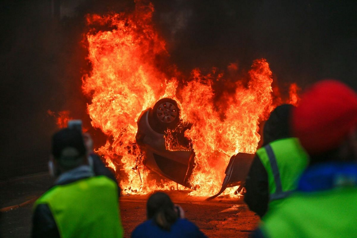 Demonstrators stand in front of a burning car during a protest of Yellow vests (Gilets jaunes) against rising oil prices and living costs, on December 1, 2018 in Paris. PHOTO: AFP