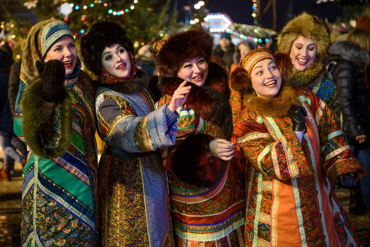 Women in traditional costumes entertain the visitors at the Christmas market on the Red Square in Moscow on December 2, 2018. PHOTO: AFP