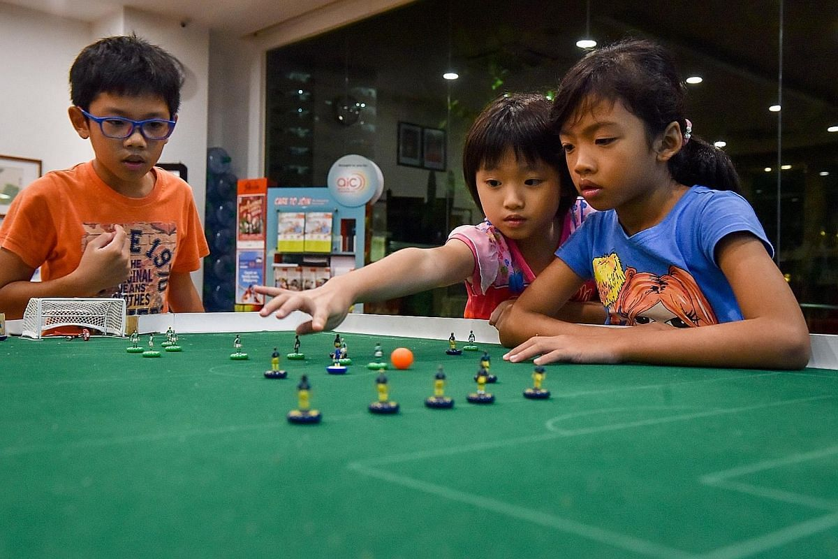 Isaac Lim (at left), 13, playing a friendly game with his father Bernard Lim, 46, while his brother Luke (face hidden), 15, acts as the referee. Memorabilia from over 10 years of competitions, these old Subbuteo footballs are now too brittle to play
