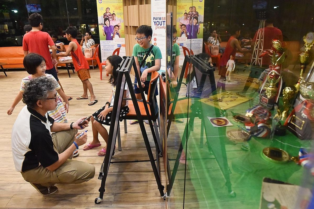Mr John Edwards, 57, one of the older active players in the community, listing down the fixtures for players taking part in a competition at Kebun Baru Community Club while young players wait for the matches to start.